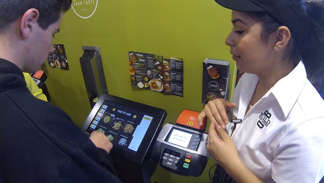 "Amy Sanchez (right) helps Michael Slade, 16, order a customized sandwich using a tablet. The ""Create Your Taste"" menu program is an experiment being conducted in four McDonald's restaurants in Orange County, Calif."