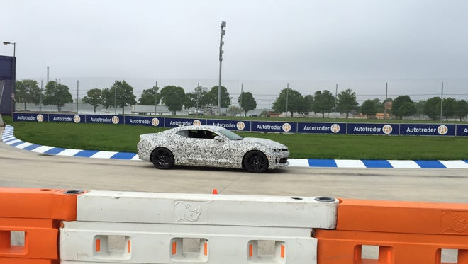 A camouflaged 2016 Chevrolet Camaro V6 on a hot lap around the Detroit Grand Prix course.