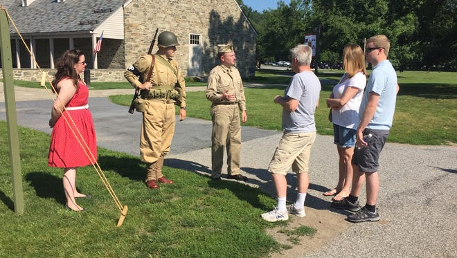 Kevin Thomas, a National Park Service ranger,  speaks to the Roberts family of London about the 240th Military Police battalion Saturday at the Franklin D. Roosevelt Presidential Library and Museum in Hyde Park. A left is Amina Thomas,  29, of Cornwall, and Joe Trocino, 28, of Hyde Park. who is dressed along with Kevin Thomas in the military police khakis. Amina Thomas was representing the home front during Saturday's living history display.