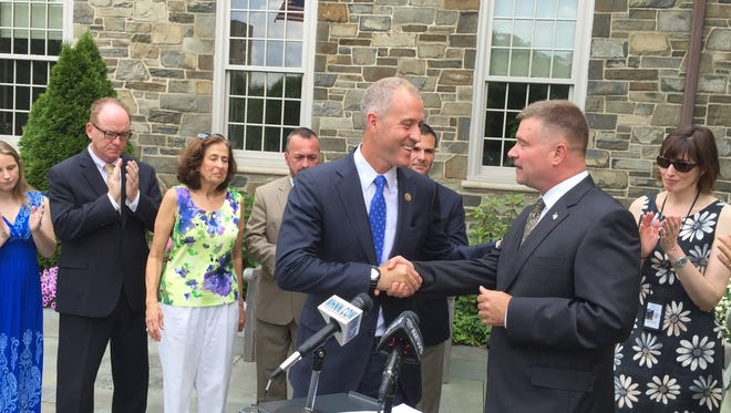 U.S. Rep. Sean Patrick Maloney, left, D-Cold Spring, shakes hands with U.S. Rep. Chris Gibson, R-Kinderhook, during a press conference at the Poughkeepsie Journal building Monday to highlight federal legislation that would prioritize research into Lyme disease.