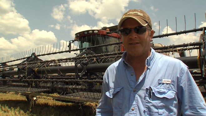 Acadia Parish Rice Farmer Tommy Frey stands in front of his combine after a long day harvesting rice.  Frey said his yields are down significantly from last year, but will be back in his fields next year.