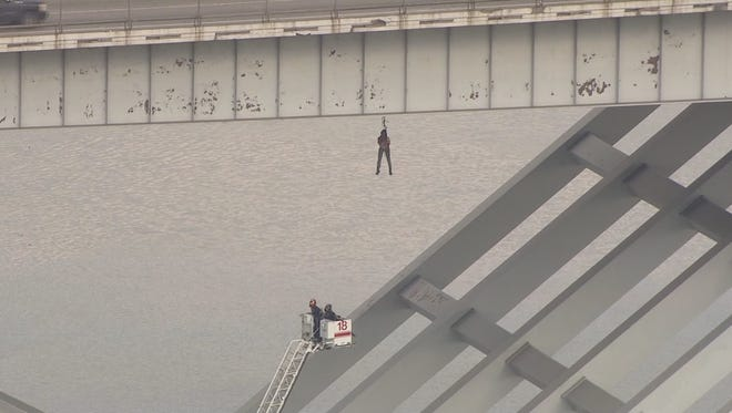 The Houston Fire Department sent high-angle ladder trucks to rescue a man dangling from the Ship Channel Bridge, but he was out of their reach.