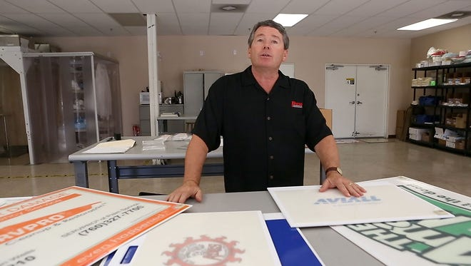 Dennis Baldwin, president and owner of Purus International shows some of the custom adhesive floor mats that his company makes that use an adhesive to remove dirt and debris from the bottom of shoes.  Baldwin's company operates out of Indio.
