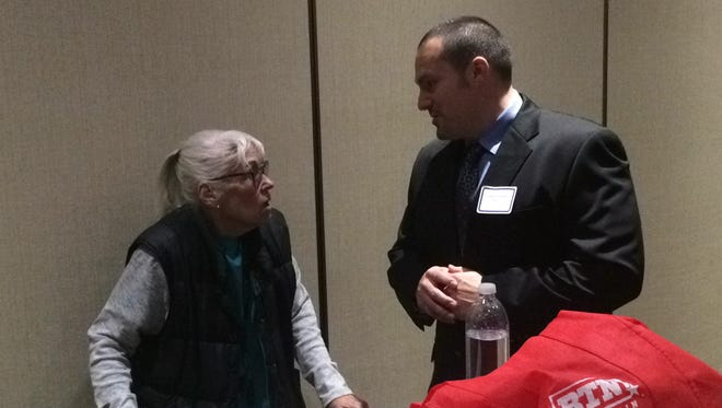 """Aaron Goldstein, a captain with the Fond du Lac Police Department, talks with Jane Daugherty of Oshkosh during a """"meet and greet"""" Monday, Nov. 16, 2015, for the Oshkosh police chief finalists."""