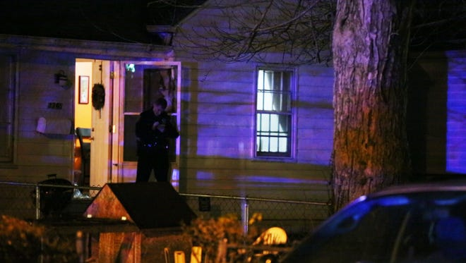 An IMPD officer stands at the front door of a home where a woman was found shot to death late Monday night. Police said two children were inside the home at the time of the shooting. The woman's husband has been charged with her murder.