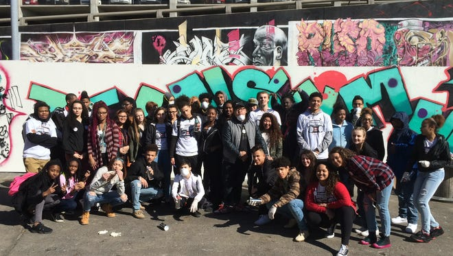 A local street-artist who goes by Asphate taught Des Moines students how to paint a graffiti mural Friday in the Des Moines Social Club courtyard.