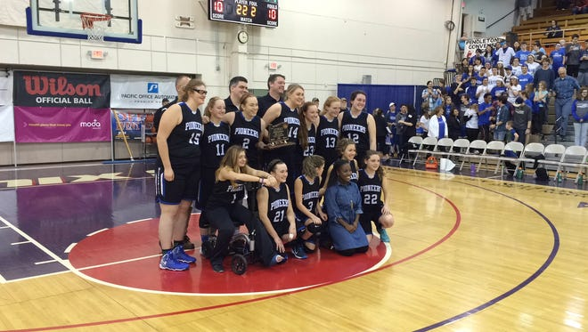 The Western Mennonite girls basketball team accepts the third-place trophy at the OSAA Class 2A state tournament.