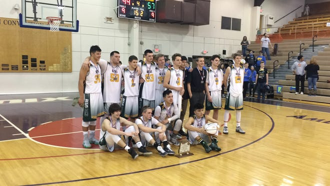 The Regis boys basketball team accepts the second-place trophy Saturday at the Class 2A state tournament.