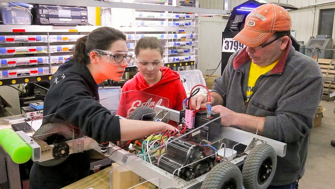 From left, senior Emilie Guermeur, of Horseheads,  freshman Alyssa Becraft of Elmira, and mentor Jeff Domey of Big Flats, work on one of Notre Dame's robots. Domey works at Corning Inc. in research and development.