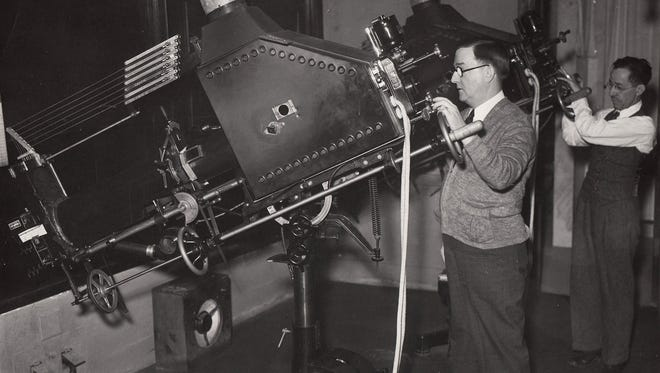 """Projectionists at work at Detroit's Michigan Theatre in downtown Detroit. The Michigan is one of the theaters featured in """"The Dying of the Light,"""" about how the advance of digital culture has affected the art of film projection."""