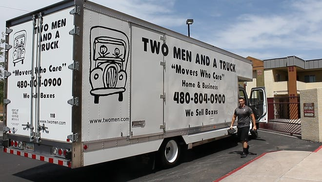 Two Men and a Truck moving company unloads boxes of essential-care items at the UMOM shelter.