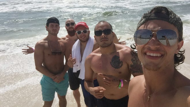 Timber Hatfield, Talon Craycraft, Mason Hatfield, Fernando Chavez and Jefferson Reddoch take a photo on the beach during their vacation to Panama City, Florida. Three of the group members were almost killed after a rip current took them far away from shore.