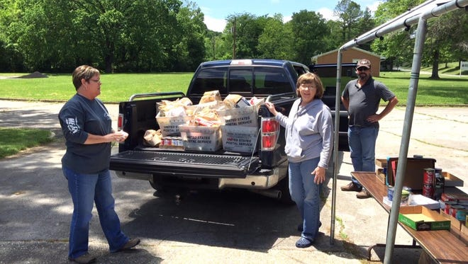 Volunteers help bring in donated food for the Bethesda Mission.
