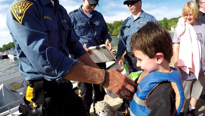 Giancarlo Kestenholz returns items from a capsized boat to State Police.