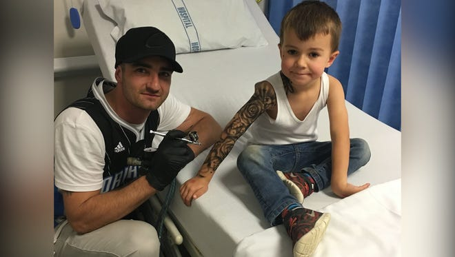 Artist Benjamin Lloyd gives a temporary tattoo to a child in the hospital.