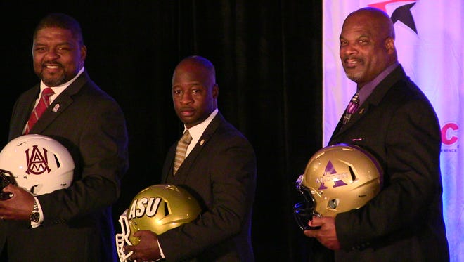 Standing between James Spady and Fred McNair, Alabama State coach Brian Jenkins poses for pictures Friday at SWAC Media Day in Birmingham.