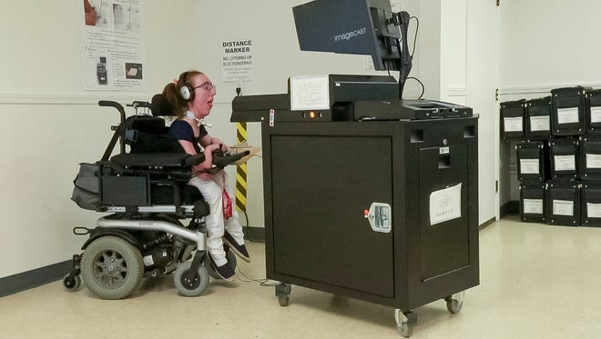 Erin Vallely, a rising Wells College senior from Dryden, reads and listens to the instructions for using the assistive voting technology that is a part of every voting machine in Tompkins County. Vallely tested the machines at the Tompkins County's Board of Elections storage facility on Hanshaw Road in the Town of Dryden.