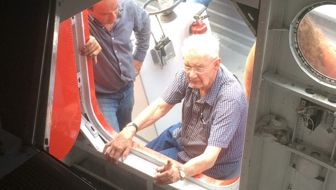 World War II veteran Clifford Graveen, right, looks inside the Hawaii Mars on Sunday at the EAA Seaplane Base on Lake Winnebago. Graveen, 89, of Green Bay worked as an electrician on the water bomber while serving in the U.S. Navy in 1946.