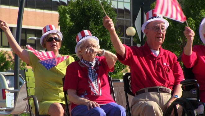 From left, Ganton Senior Communities employee Marty Duncan and residents Catherine Crowell and Stan Macey move to patriotic music at Wednesday's Battle Creek Farmers Market.