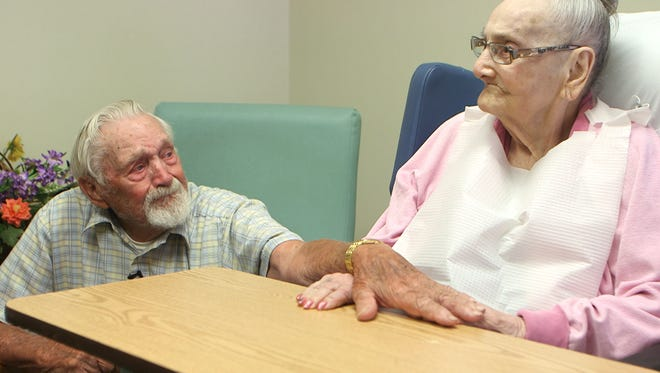 Frank Korker holds the hand of his wife Lola at Bartley Healthcare Nursing and Rehabilitation in Jackson. They've been married 71 years.