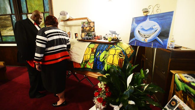 """Some of Tae's favorite toys, paintings and personal items are placed in and around his casket at his funeral service in Findlay. Tae's parents, with the help of various organizations and private donors, helped him complete a """"bucket list"""" in his final months."""