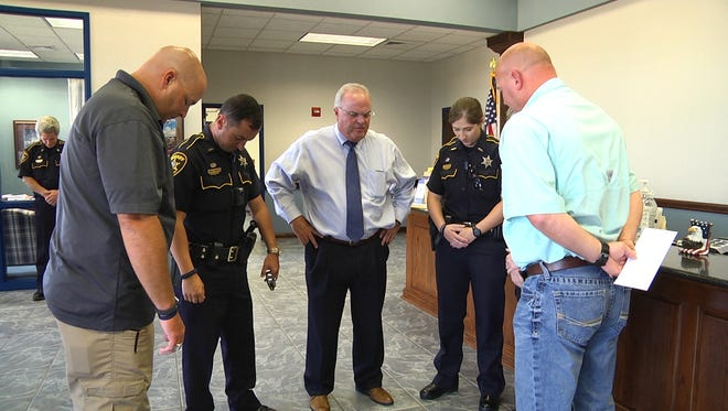 Bossier deputies say a prayer before departing for South Louisiana.