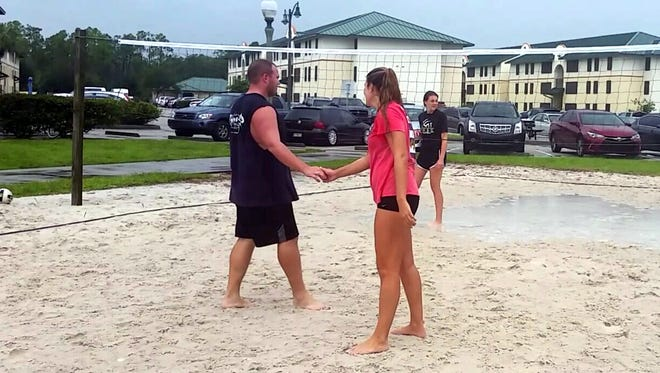 Florida Gulf Coast University students William Ninesling, 21,(left)  and Madison Stowe, 20, congratulate each other during a volleyball game at North Lake Village, a campus living facility. FGCU plans to enhance the living experience at North Lake  by adding a dining facility.