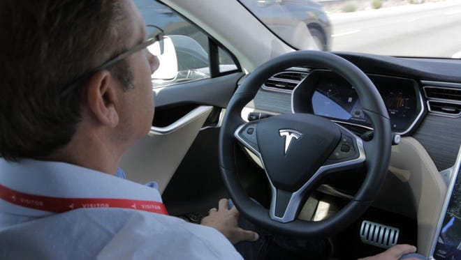 USA TODAY tech reporter Marco della Cava takes his hands off the wheel of a Tesla Model S sedan while driving down the 280 Freeway north of the Tesla's headquarters in Palo Alto, Calif.