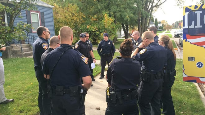 Second-shift Oshkosh police officers meet for a daily briefing, Wednesday, Oct. 19, 2016, in the 800 block of West Seventh Avenue, where they say they've been having ongoing drug and other issues at a home.