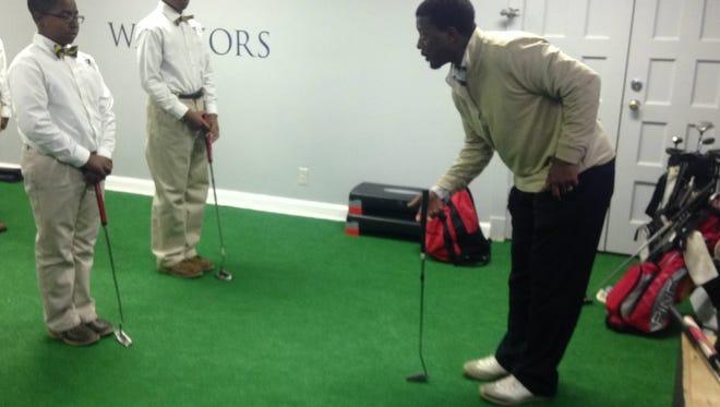 Scholars at Valiant Cross Academy learn golf from coach Quincy Leonard.