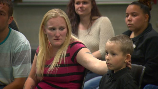 Xzayvier's mother supports him as they listen to a presentation in his honor.