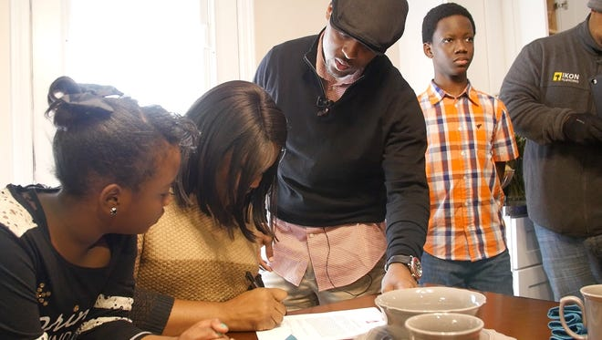 Rickita Burney, second from left, signs papers to take ownership of her new home with help from Warrick Dunn, center.