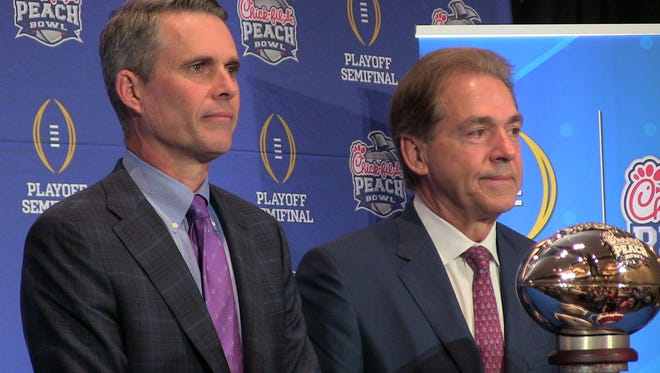 Washington coach Chris Petersen and Alabama coach Nick Saban pose with the Chick-fil-A Peach Bowl trophy Friday.