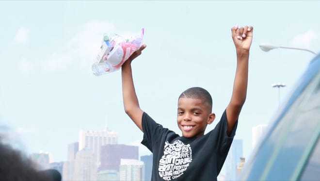 """Jahkil Jackson, 9, hands out his """"Blessing Bags"""" to homeless people."""