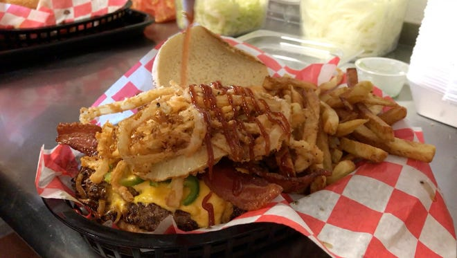 The BBQ Bacon Butch Burger is finished with a drizzle of barbecue sauce at Butch's Famous Burgers in North Fort Myers.