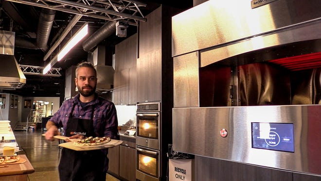 Justin Berger gets ready to load a pizza into the Monogram Pizza Oven at GE Appliance's FirstBuild.