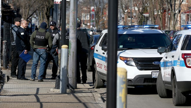 Chicago police stand near where a toddler and a man were fatally shot and a woman was wounded near Ogden and Kostner avenues in the Little Village neighborhood of Chicago Tuesday, Feb. 14, 2017. Police are examining dramatic video that captured the shooting that killed a toddler and a man authorities say was the intended target.