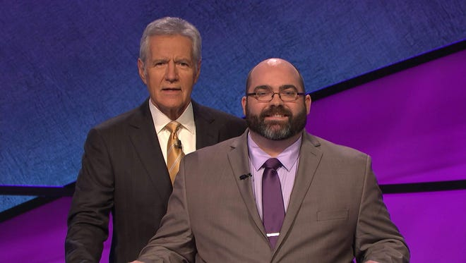 """Loyal graduate Trevor Mahoney poses for a picture with host Alex Trebek during an appearance as a """"Jeopardy!"""" contestant."""