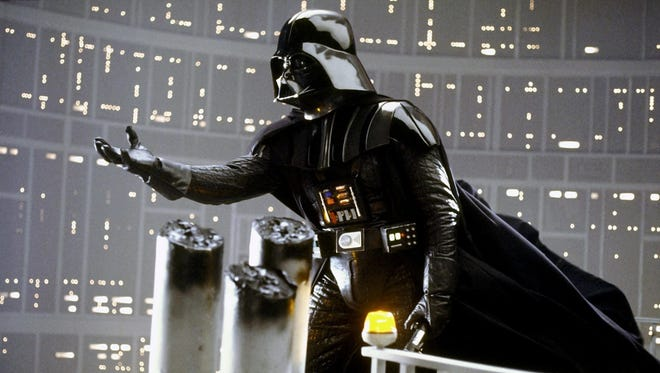 """Darth Vader looks like he could be conducting an orchestra performance of his own """"Imperial March"""" in this still from """"The Empire Strikes Back."""""""
