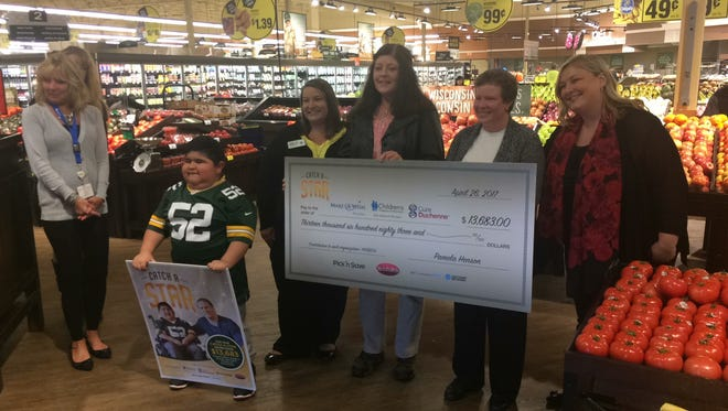 Angel Cruz helped present a $14,000 check to the Children's Hospital of Wisconsin and Make-A-Wish Wisconsin on Wednesday at Pick 'n Save, 1900 Jackson St., Oshkosh.