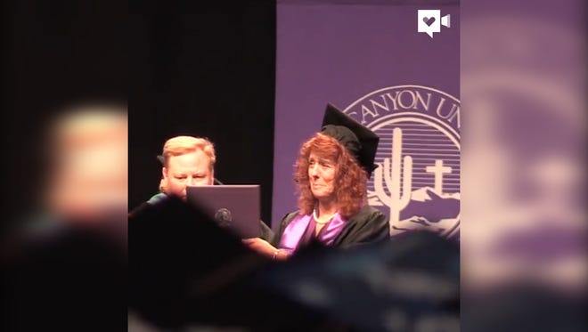 Cathy Hocking accepts a diploma on behalf of her daughter, Karli Richardson, during Grand Canyon University commencement in Phoenix on April 27, 2017. Karli and her sister, Kelsey, were both killed in the wrong-way crash on I-17 on Good Friday. Hocking said she was proud to accept her daughter's diploma that recognized all of her hard work.