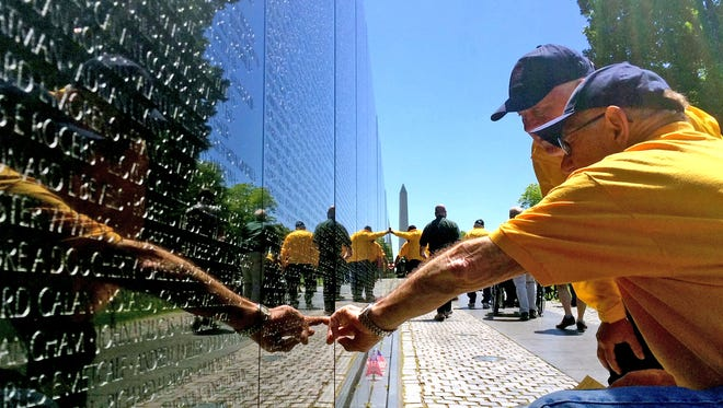 John Brandenburg of Rhinelander touches a name engraved on the Vietnam Veterans Memorial in Washington, D.C., on May 15, 2016, on a Never Forgotten Honor Flight while Cal Doering of Gleason looks on.
