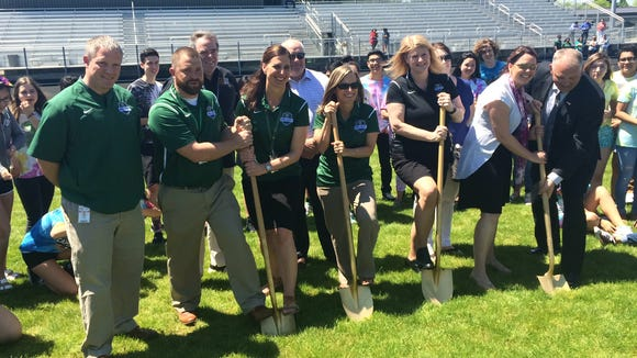 McKay officials and boosters celebrate breaking ground on the new artificial turf field project at the school.