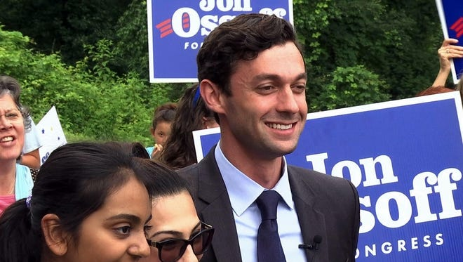 Democrat Jon Ossoff poses for a picture with supporters outside of the East Roswell Library in Roswell, Ga.,