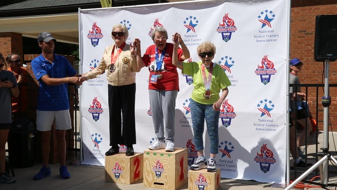 Ann McGowan, right, pictured with Fay Bond and Wally Dashiell, at the Women's shot put medal ceremony.