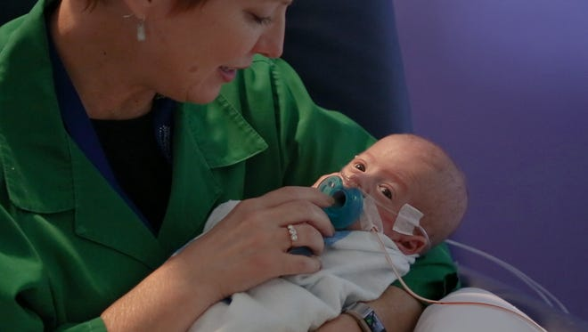 Noah, a preemie at Children's Healthcare of Atlanta, is snuggled by a volunteer.