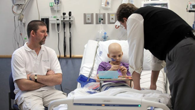 Cancer patient Emily Whitehead was hospitalized at age 6 during an experimental therapy, led by Dr. Stephan Grupp, right, a doctor at the Children's Hospital of Philadelphia and the University of Pennsylvania's Perelman School of Medicine.