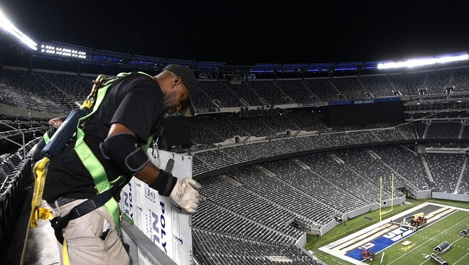 MetLife Stadium operations workers change the Ring of Honor panels that line the upper deck of the stadium. They have to switch 114 panels in total. The Giants hosted the Steelers for a preseason game at 7 p.m. Friday, and the Jets hosted the Titans at 7:30 p.m. on Saturday.