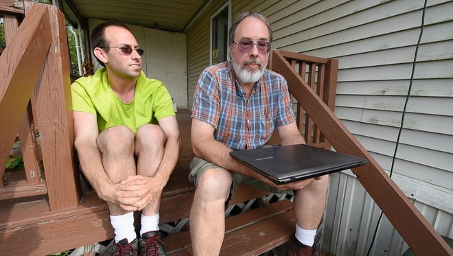 Andrew Bolton, left, and his father Stanley Bolton II, with the recovered laptop at Andrew's home in Dover Township. The laptop was taken by the York County District Attorney's office through civil asset forfeiture. The Boltons had to fight in the courts to get the laptop returned to them.
