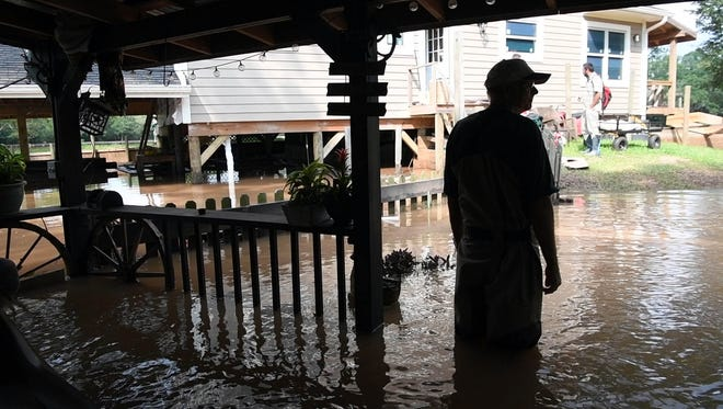 Tom Powell takes a moment on the porch of his flooded cottage after viewing the extensive damage done by Hurricane Harvey in Fort Bend.